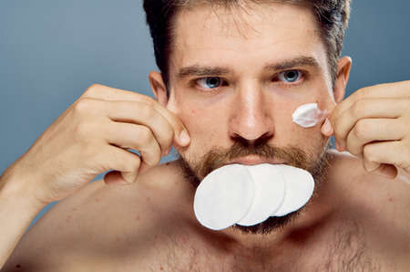 Man with a beard on a background of a background, wadded disks, cosmetic cream, health, beauty.