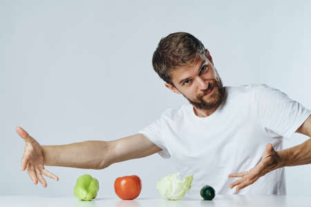 Man with a beard on a light background at a table showing vegetables, diet, vegetarianism.