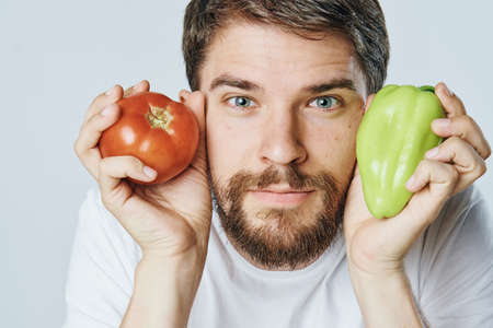 Man with a beard on a light background holds vegetables, peppers, tomato, diet, vegetarianism.