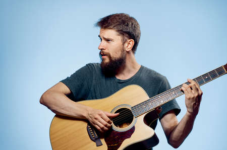 plucking: Man with a beard on a blue background playing the guitar, emotions, musical instruments.