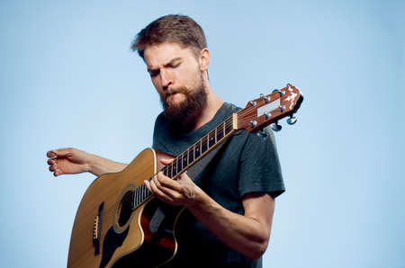 plucking: Man with a beard playing the guitar on a blue background, musical instruments.