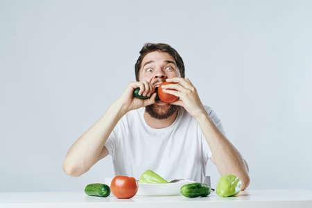 Mann mit einem Bart auf einem hellen Hintergrund an einem Tisch Gemüse essend, Diät, Vegetarier.