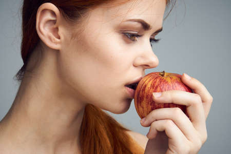 Young beautiful woman on a gray background holds an apple, diet. Stock Photo
