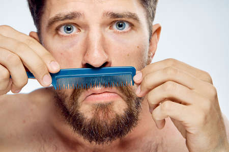 Man with a beard on a light background combs his mustache, portrait. Stock Photo