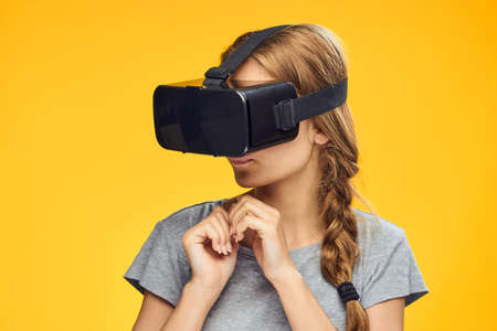 Young beautiful woman in glasses of virtual reality on a yellow background.
