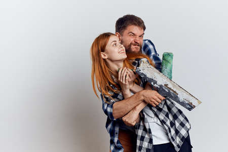 Young beautiful woman on white isolated background with bearded man holding construction tools for repair. Stock Photo