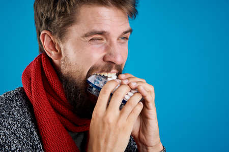 blowing nose: Man with a beard on a blue background eating slabs of pills Stock Photo