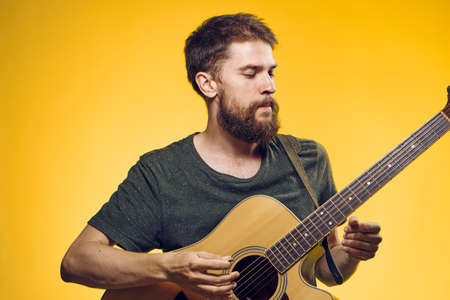 plucking: A man with a beard holds a guitar on a yellow background, musical instruments, a musician. Stock Photo