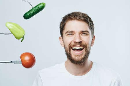 Mann mit einem Bart auf einem hellen Hintergrund, Lächeln, Porträt, Gemüse, Diät, Vegetarier.