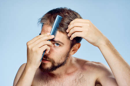 Man with a beard on a blue background combs his hair.