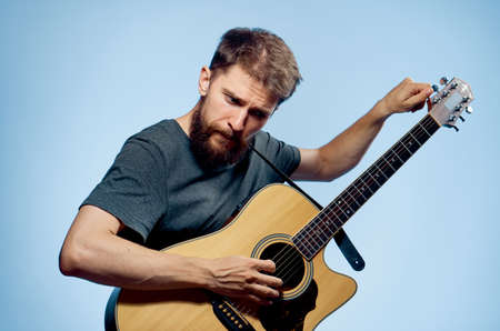 A man with a beard on a blue background tunes a guitar, musician, music.
