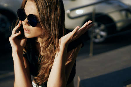 Beautiful young woman in sunglasses calling on the phone in the street in the city.