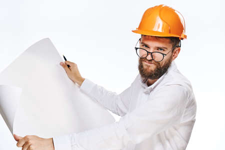 Engineer with a beard holding a drawing on white isolated background in a helmet.