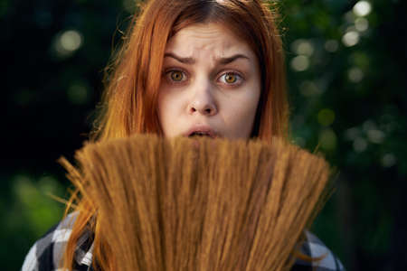 Young beautiful woman holds a broom in the garden, gardener, portrait, emotions. Stock Photo