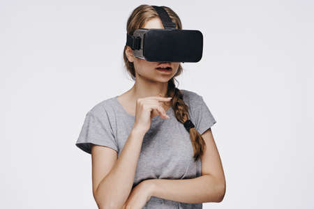 Young beautiful woman in glasses virtual reality on white isolated background.