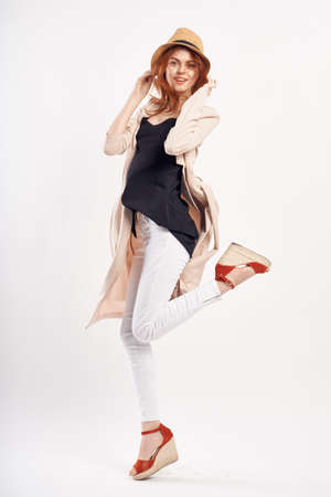 Young beautiful woman in a hat on a white background, full-length, jump, fashion.