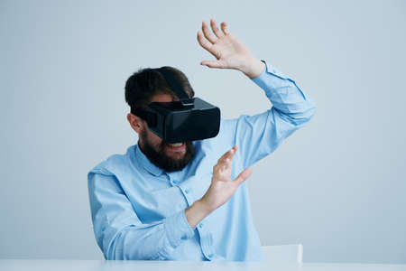 breaking: Man with a beard in glasses of virtual reality on a light background, portrait, entertainment. Stock Photo