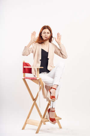 Young beautiful woman in glasses on a white isolated background sitting on a stool in full growth, fashion.