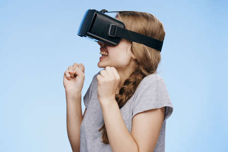 Young beautiful woman on a light blue background with virtual reality glasses.