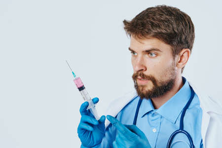 A man with a beard on a light background holds a syringe in a medical dressing gown, doctor.