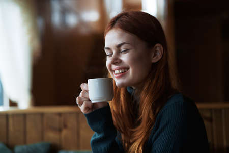 Young beautiful woman drinks coffee in a cafe, winter.