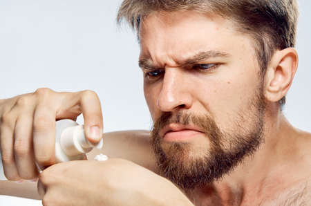 mirror image: Man with a beard on a light background applies cosmetic cream, portrait, emotions.