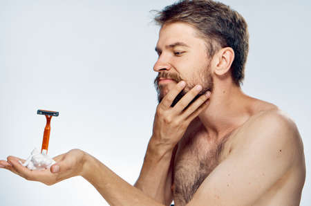 mirror: A man with a beard on a light background holds a razor and shaving foam.
