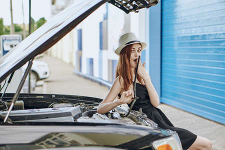 Young beautiful woman in a hat repairing a car outdoors in the city, body shop.