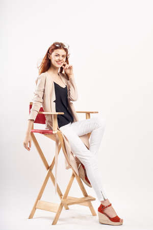 Young beautiful woman on white isolated background sits on high chair, smile, emotion, full-length.