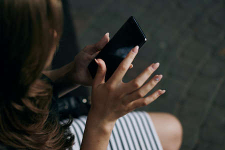 nails: Woman holding a phone, close-up, hands, nails. Stock Photo