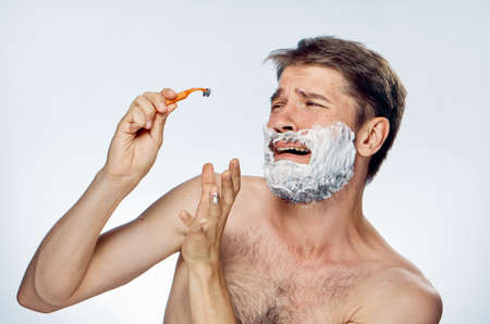 A man with a beard on a light background holds a razor in shaving foam. Stock Photo