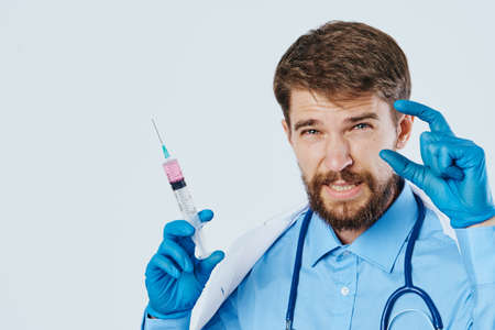 Man with a beard on a light background in a medical dressing gown holds a syringe, portrait, blank space for copying.