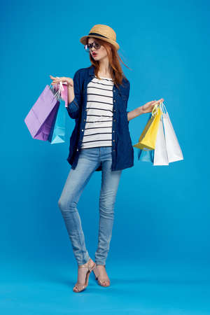 Beautiful woman on a blue background wearing a hat and glasses holding packages, shopping, shopaholic. Stock Photo