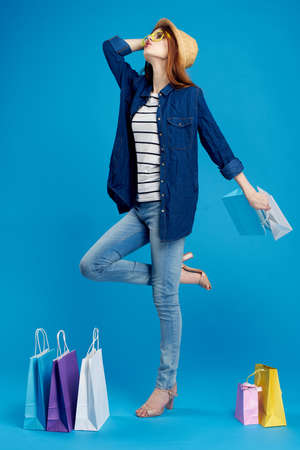 Beautiful young woman in glasses and in a hat holds many packages on a blue fennel, full-length, shopping, shopaholic.