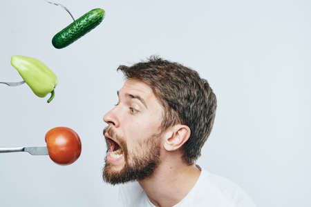 Man with a beard against a light background, vegetables, forks, diet, vegetarianism.