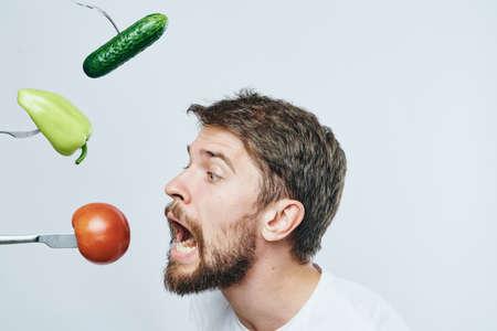 Mann mit einem Bart gegen einen hellen Hintergrund, Gemüse, Gabeln, Diät, Vegetarismus.