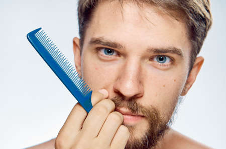metrosexual: Man with a beard on a light background holds a comb, portrait.