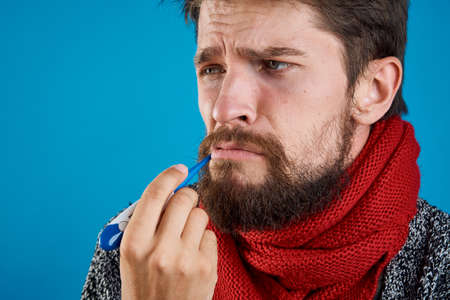 A man with a beard on a blue background holds a thermometer in his mouth, a portrait, an empty space for copying, a flu, a disease, a patient.