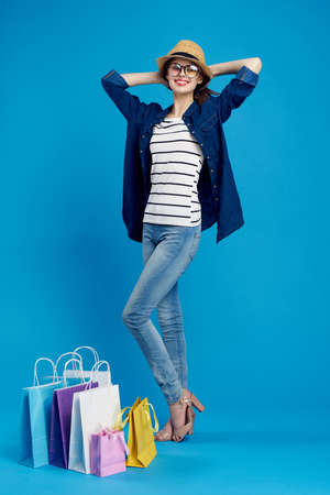 Young woman in a hat and glasses in full growth on a blue background, packages, shopping, shopaholic. Stock Photo