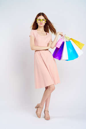 young woman holds packages in yellow glasses. Stock Photo