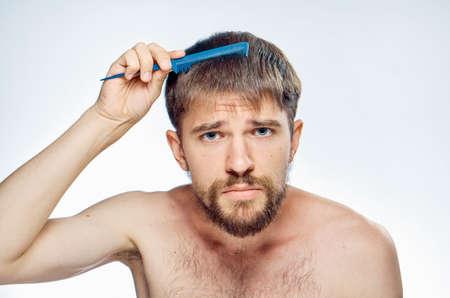 metrosexual: the man is combing his hair.