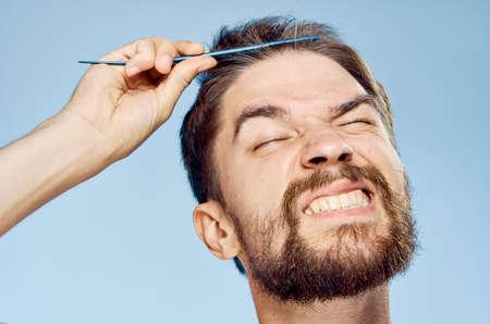 Man combing his hair, portrait.
