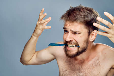 man holding a comb in his teeth.