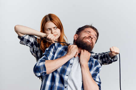 a woman strangling a man with a cord.