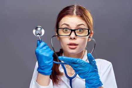 woman doctor holding a stethoscope, portrait, emotion, black background. Stock Photo