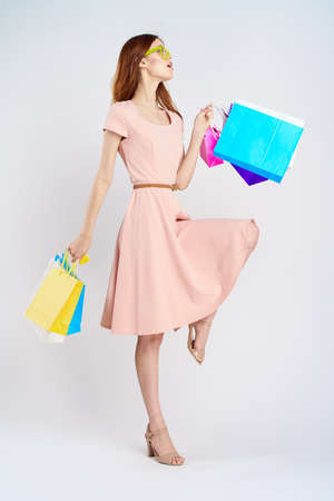 Beautiful woman in pink dress holds many packages. Stock Photo