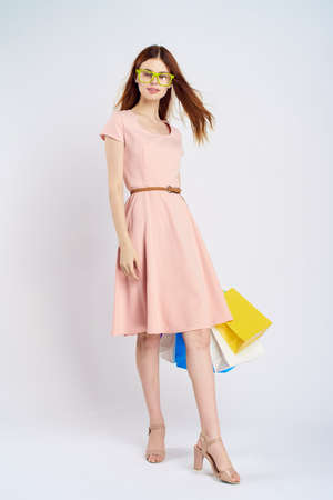 beautiful woman in pink dress and yellow glasses holds packages on white background.