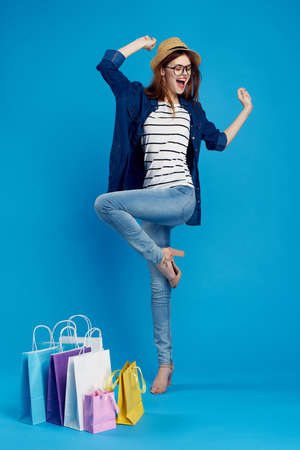 woman in glasses and in a hat jumps on a blue background, shopping.