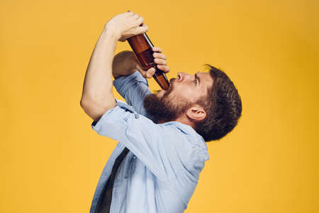 a man is drinking beer on a yellow background.