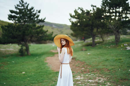 e85fed57ee7 woman with hat and white dress in the mountains. Stock Photo
